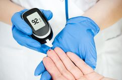 Doctor woman measuring glucose level blood Stock Photo