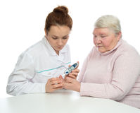 Doctor woman measuring glucose level blood test with glucometer Stock Photos
