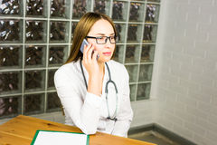 Doctor woman in medical office smiling and talking on the phone Stock Images