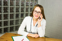 Doctor woman in medical office smiling and talking on the phone royalty free stock photo