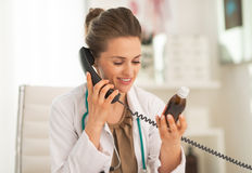 Doctor woman with medicine bottle talking phone Royalty Free Stock Photography