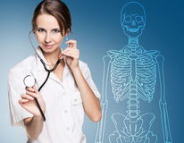 Doctor woman pointing on drawing human skeleton. Royalty Free Stock Photos