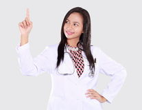 Doctor woman is pointing upwards. Isolated on white background Royalty Free Stock Images
