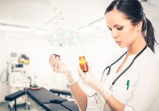 Doctor woman reading prescription on a vial Royalty Free Stock Images