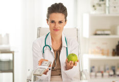 Doctor woman showing apple and pack of money. In her modern office Stock Images