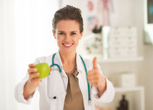 Doctor woman showing apple and thumbs up Stock Photo