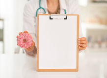 Doctor woman showing blank clipboard and donut Stock Image