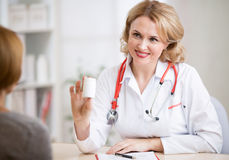 Doctor woman showing medicine can to patient in Royalty Free Stock Images