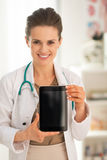 Doctor woman showing tablet pc blank screen. Happy medical doctor woman showing tablet pc blank screen Stock Photo