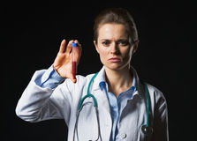 Doctor woman showing test tube on black background Stock Image