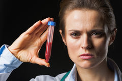 Doctor woman showing test tube isolated on black Royalty Free Stock Photo