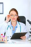 Doctor woman sitting at table with clipboard Royalty Free Stock Photos