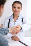 Doctor woman smiling while shaking hands with her male patient. Medicine and trust concept. Doctor women smiling while shaking hands with her male patient Royalty Free Stock Photography