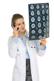 Doctor woman speaking phone and looking on MRI Royalty Free Stock Photo