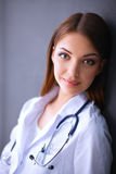 Doctor woman with stethoscope isolated on grey background. Young doctor woman with stethoscope isolated on grey background Royalty Free Stock Photography