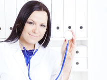Doctor woman with stethoscope in office Stock Photos