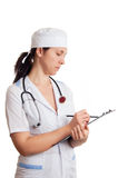 Doctor woman with stethoscope writing in papers Royalty Free Stock Image