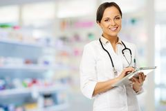 Doctor woman with tablet pc. Young positive brunette doctor woman in drug store with tablet pc Royalty Free Stock Photography