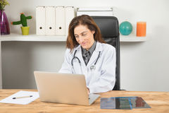 Doctor woman using laptop in workplace. Brown hair doctor woman, with white gown and stethoscope, sitting in wooden table smiling and typing in portable laptop Stock Photo