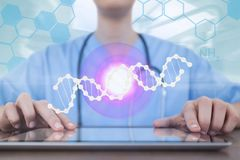 Doctor woman using a tablet with DNA strand and flares Stock Photo