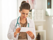 Doctor woman using tablet pc in office. Doctor woman in white robe using tablet pc in office Stock Photo