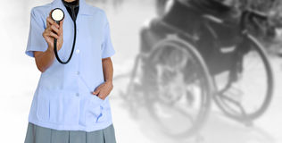 Doctor woman wearing white medical uniform and holding stethoscopes and patient sitting on wheelchair stock photography