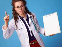 Doctor woman with clipboard and raised fingers drawing attention Stock Images