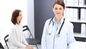 Doctor woman at work. Portrait of female physician cheerful smiling while standing near reception desk at clinic or royalty free stock photography