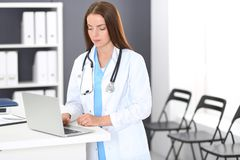 Doctor woman at work. Portrait of female physician using laptop computer while standing near reception desk at clinic or. Emergency hospital. Medicine and royalty free stock images