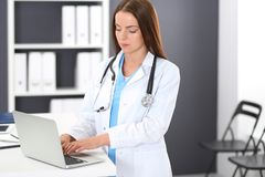Doctor woman at work. Portrait of female physician using laptop computer while standing near reception desk at clinic or. Emergency hospital. Medicine and royalty free stock photography