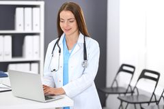 Doctor woman at work. Portrait of female physician using laptop computer while standing near reception desk at clinic or. Emergency hospital. Medicine and stock photos