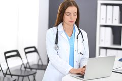 Doctor woman at work. Portrait of female physician using laptop computer while standing near reception desk at clinic or. Emergency hospital. Medicine and stock image