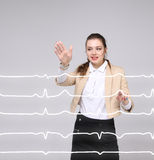Doctor woman working with cardiogram lines. Young doctor woman working with cardiogram. Electrocardiogram lines in air Royalty Free Stock Photos
