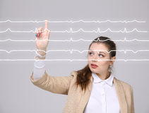 Doctor woman working with cardiogram lines. Young doctor woman working with cardiogram. Electrocardiogram lines in air Stock Photo