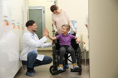 Doctor with woman and her child in wheelchair. Doctor with women and her child in wheelchair at hospital royalty free stock photo