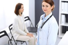 Doctor woman at work. Portrait of female physician cheerful smiling while standing near reception desk at clinic or stock photo