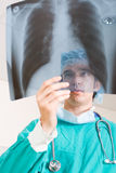 Doctor at work. Young male medical surgeon in hospital at work looking at x-ray film Royalty Free Stock Images