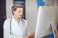 Doctor working at computer desk Stock Images