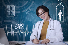 Doctor working with computer interface background. Beautiful female doctor working on the table and writes on the document with computer interface background Royalty Free Stock Photography