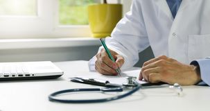 Doctor working at desk in clinics office