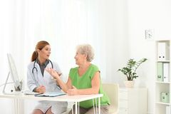 Doctor working with elderly patient in hospital. stock photography