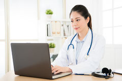 Doctor working with her computer. Global famous asian female doctor working with her computer in the office and visiting caring patient online with computer Royalty Free Stock Images