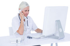 Doctor working on her laptop and calling Stock Photography
