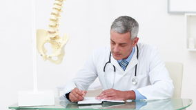 Doctor working at his desk and smiling at camera stock video footage