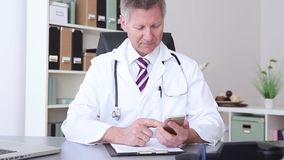 Doctor working at the hospital using a smart phone stock video footage