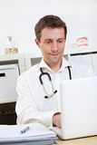 Doctor working on laptop Stock Image