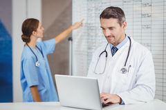 Doctor working on laptop with colleague pointing at chart Stock Photography