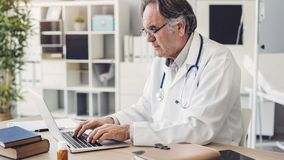 Doctor working with laptop computer royalty free stock photos