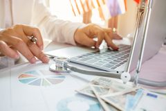 Doctor working on laptop computer with report analysis and money. About Healthcare costs and fees in medical hostpital office. Focus stethoscope on table Stock Image
