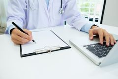 Doctor working with laptop computer and writing on paperwork. Ho Royalty Free Stock Photos